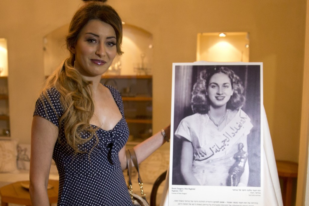 Sarah Idan, Iraq's 2017 Miss Universe beauty pageant contestant, poses with an exhibit showing 1947 Miss Baghdad Renee Dangoor, during a visit to the
