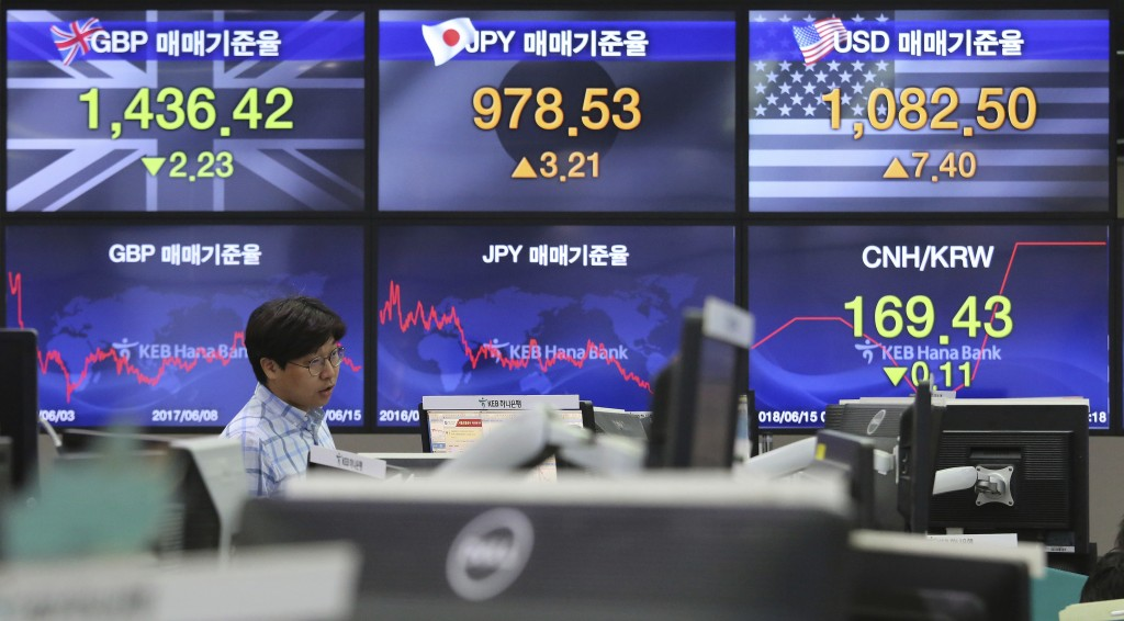 A currency trader watches monitors at the foreign exchange dealing room of the KEB Hana Bank headquarters in Seoul, South Korea, Friday, June 15, 2018...