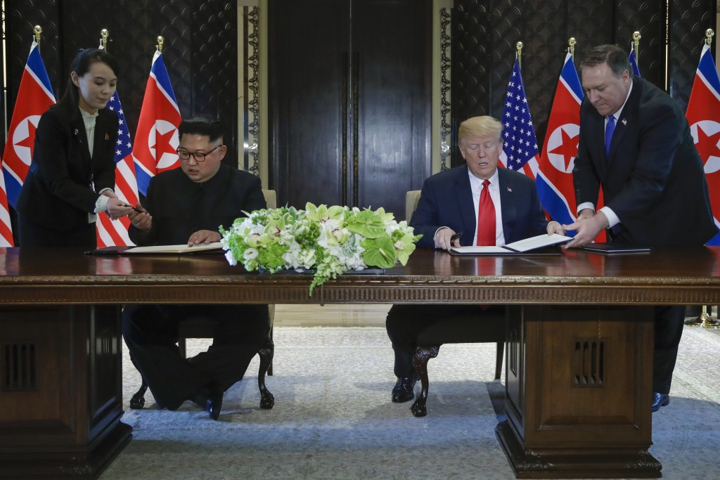 FILE - In this Tuesday, June 12, 2018, file photo, North Korea leader Kim Jong Un and U.S. President Donald Trump prepare to sign a document at the Ca...