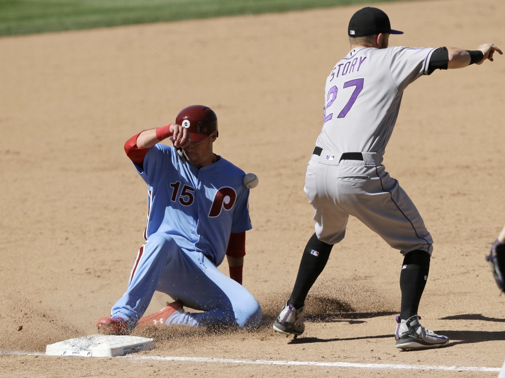 Philadelphia Phillies' Andrew Knapp, left, slides into third base past Colorado Rockies shortstop Trevor Story to advance on a ground out by Scott Kin
