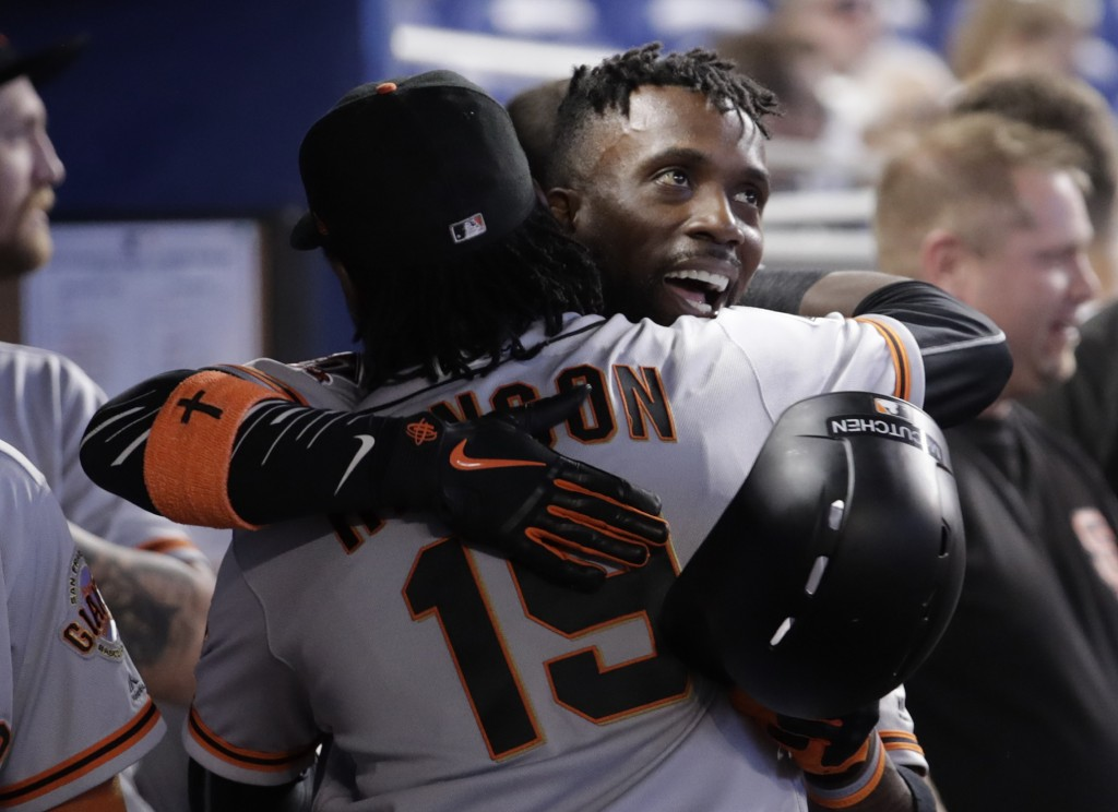 San Francisco Giants' Andrew McCutchen is hugged by Alen Hanson (19) after hitting a two-run home run during the first inning of a baseball game again