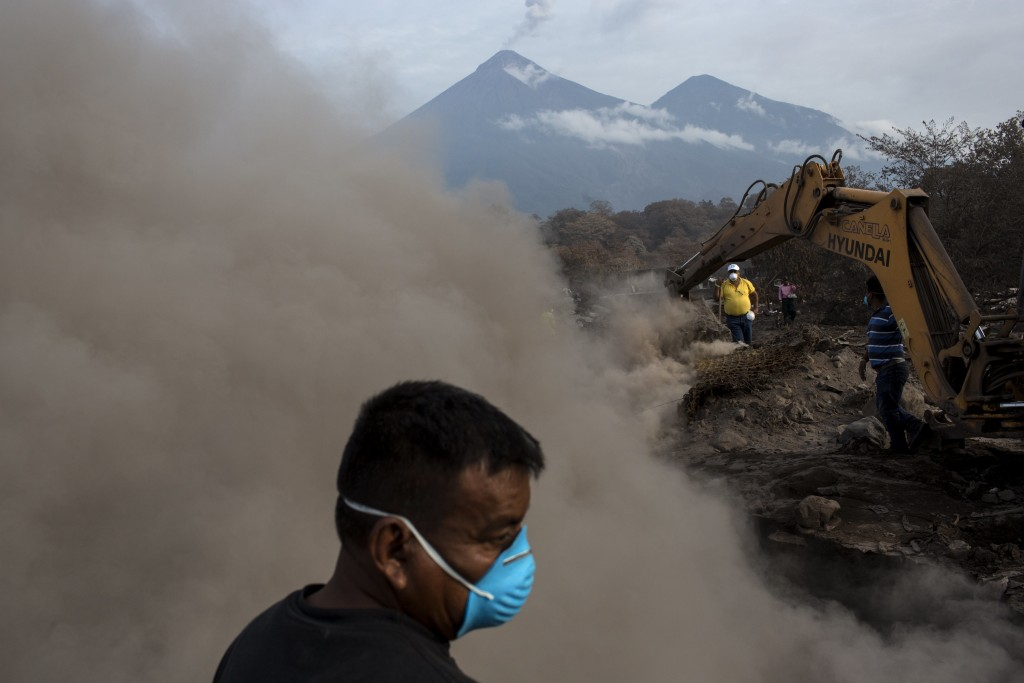 FILE - In this  June 14, 2018 file photo, Mamerto Vazquez searches for his family killed by the eruption of the Volcano of Fire at his home buried in ...
