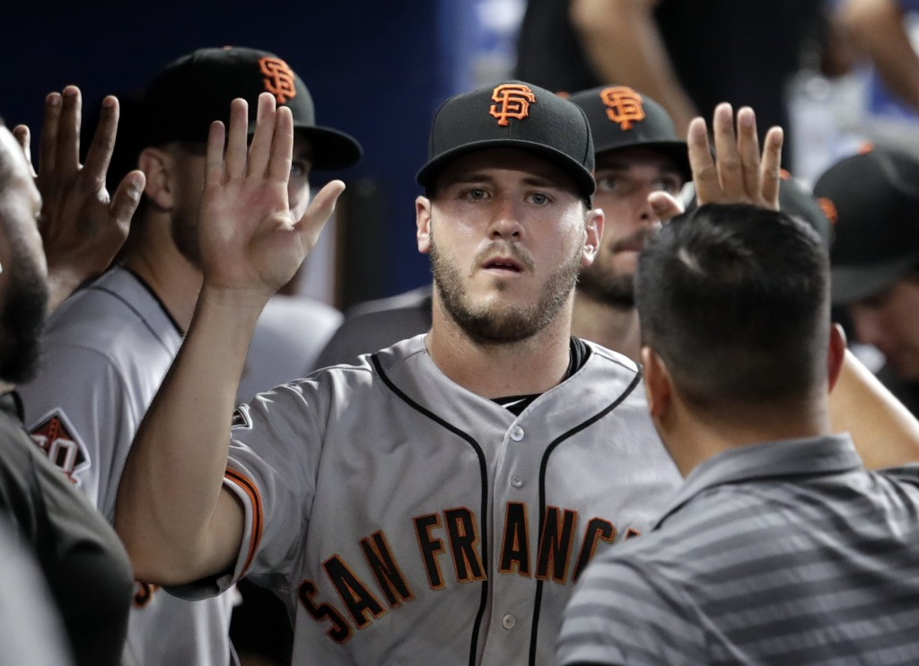 San Francisco Giants relief pitcher Ty Blach is congratulated in the dugout after being relieved in the 16th inning of a baseball game against the Mia