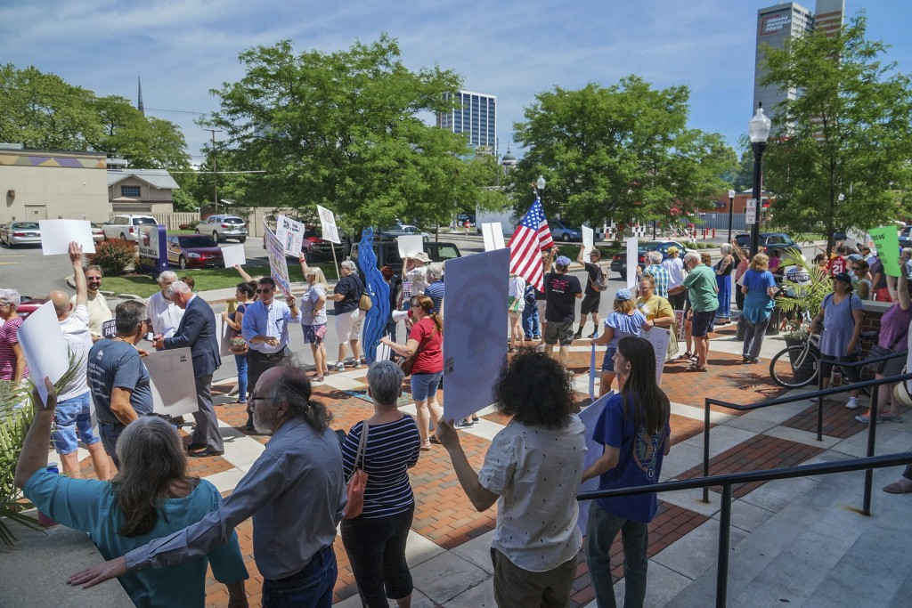 People line up to protest U.S. Attorney General Jeff Sessions and immigration reform at Parkview Field in Fort Wayne, Ind., Thursday, June 14, 2018. S