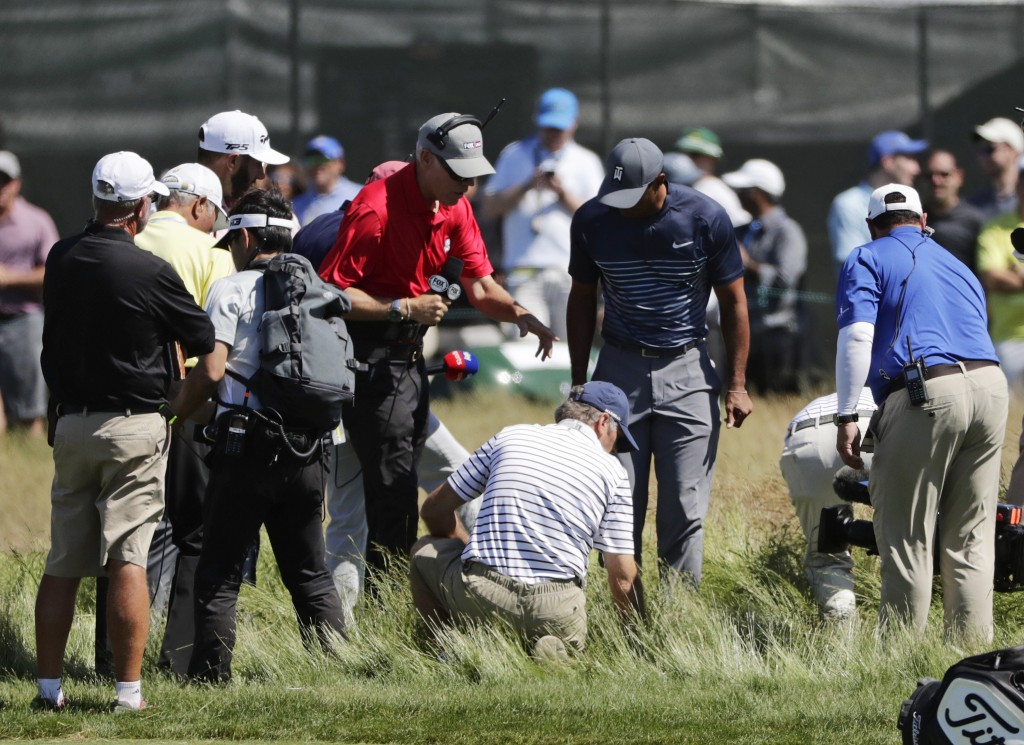 Tiger Woods, center, helps officials look for a ball hit into the fescue by Dustin Johnson on the fifth hole during the first round of the U.S. Open G