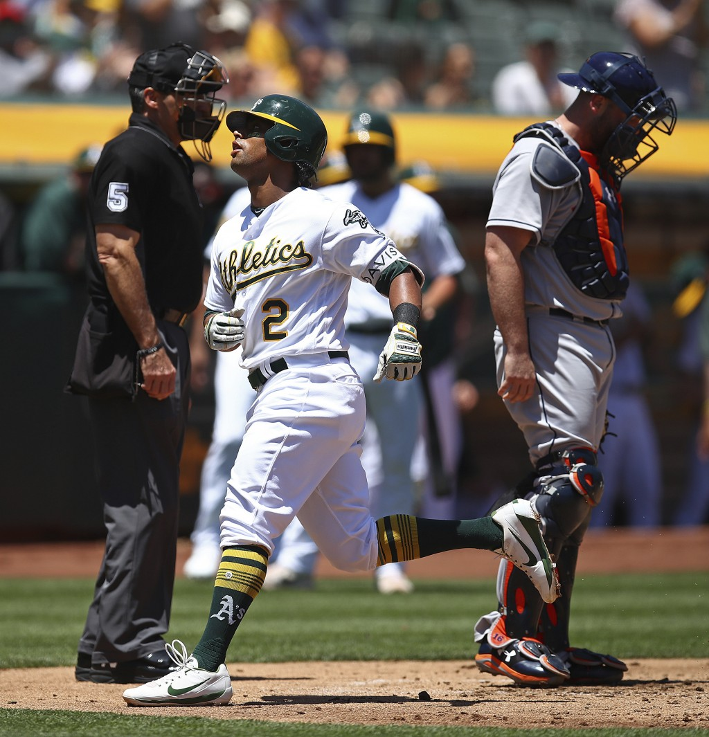 Oakland Athletics' Khris Davis (2) passes home plate and Houston Astros catcher Brian McCann, right, after hitting a home run off Justin Verlander in