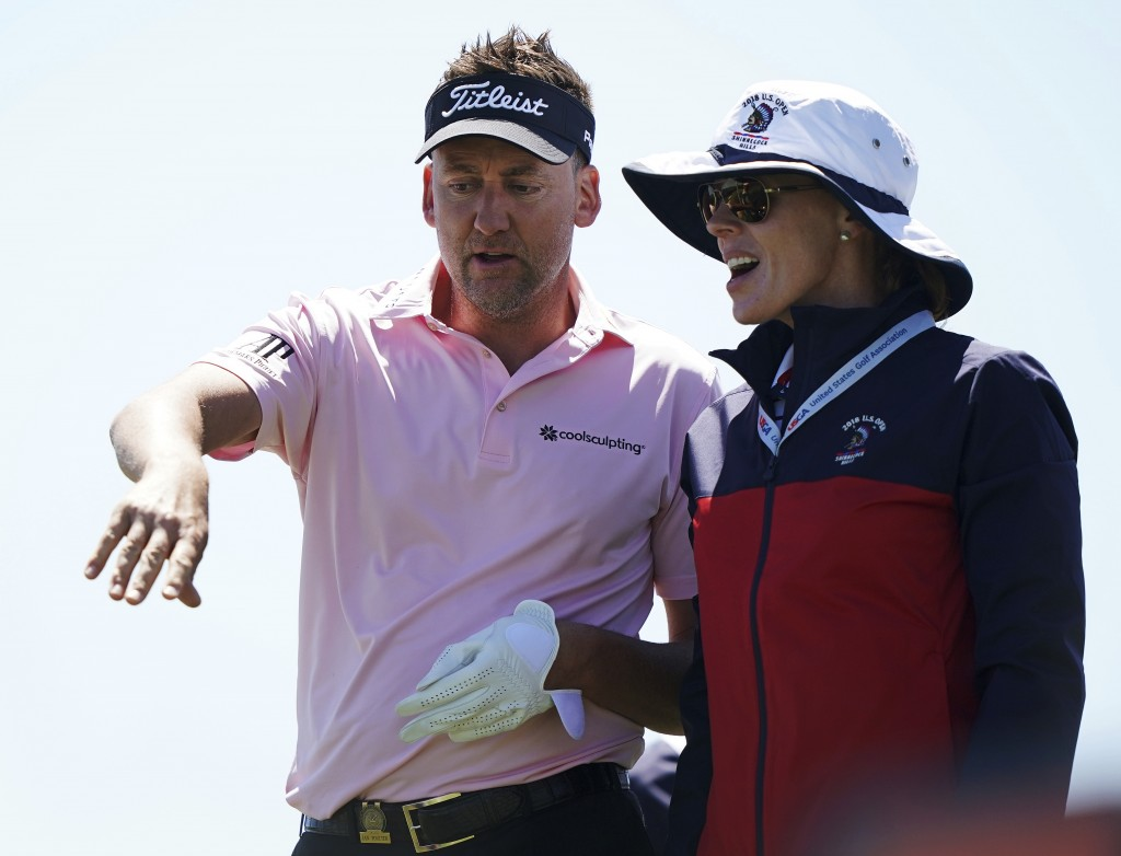 Ian Poulter, of England, talks with an official during the first round of the U.S. Open Golf Championship, Thursday, June 14, 2018, in Southampton, N.