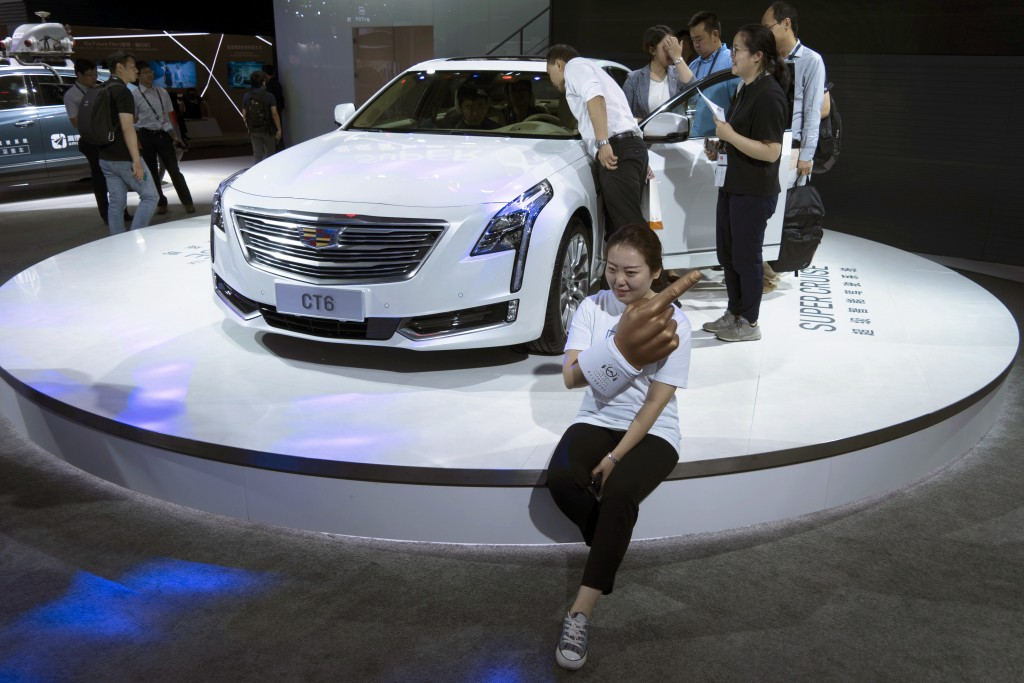 A woman poses for a photo in front of a CT6 Cadillac during the Consumer Electronics Show Asia 2018 in Shanghai, China on Friday, June 15, 2018. Presi