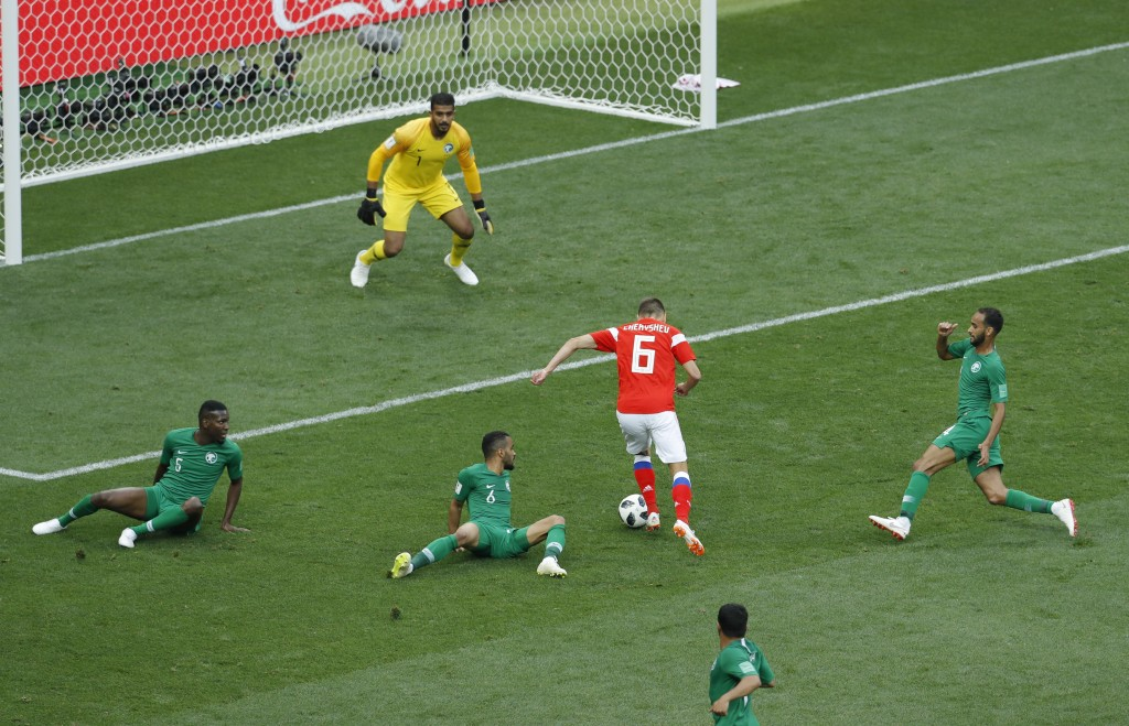 Russia's Denis Cheryshev dribbles past Saudi Arabia players to score his side's second goal during the 2018 soccer World Cup opening match at the Luzh