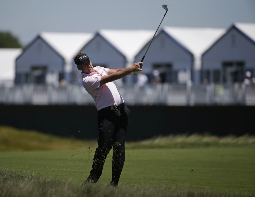 Ian Poulter, of England hits an approach shot on the 16th hole during the first round of the U.S. Open Golf Championship, Thursday, June 14, 2018, in