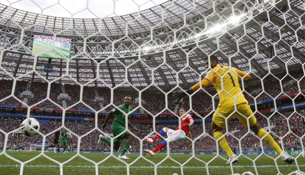 Russia's Artyom Dzyuba, center, scores his side's third goal past Saudi Arabia goalkeeper Abdullah Almuaiouf during the group A match between Russia a