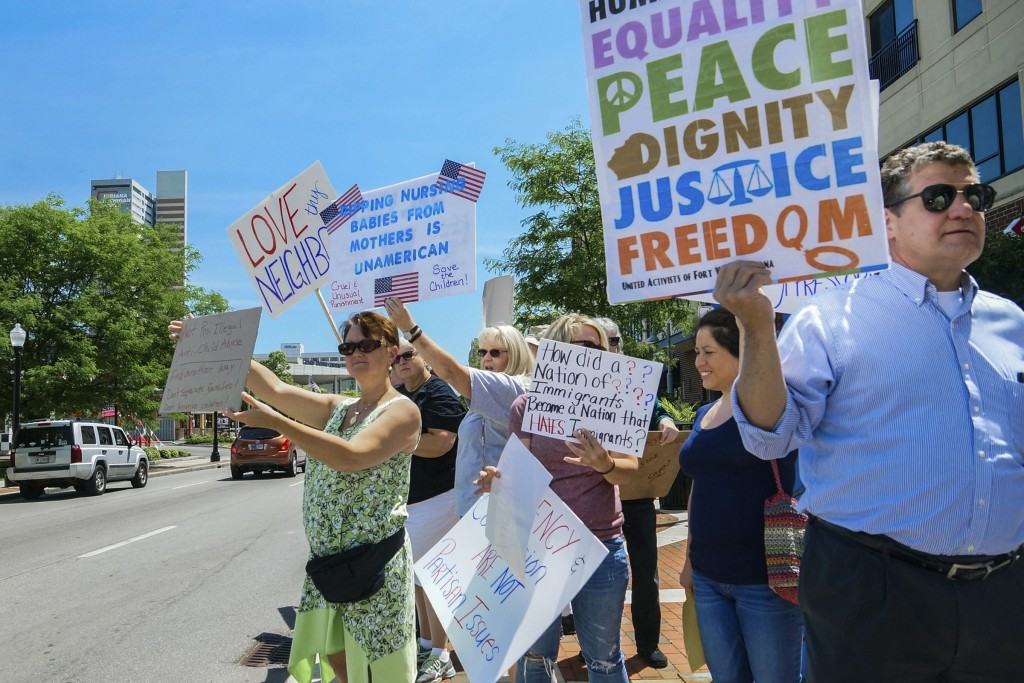 People line up to protest U.S. Attorney General Jeff Sessions and immigration reform at Parkview Field in Fort Wayne, Ind. Thursday, June 14, 2018. (M
