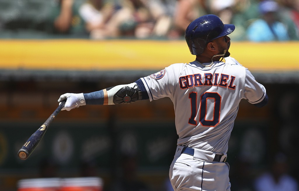 Houston Astros' Yuli Gurriel swings for an RBI double off Oakland Athletics' Frankie Montas in the first inning of a baseball game Thursday, June 14,