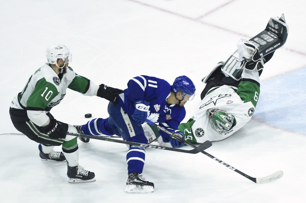Texas Stars goaltender Mike McKenna (29) poke-checks the puck away from Toronto Marlies left wing Andreas Johnsson (11) as Stars center Justin Dowling