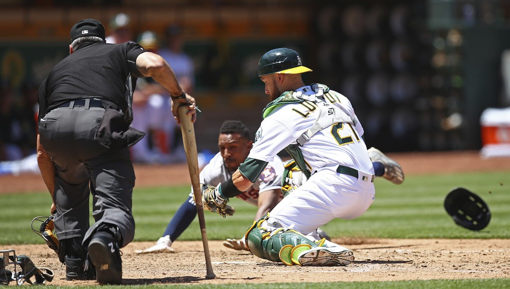 Houston Astros' Tony Kemp scores behind Oakland Athletics catcher Jonathan Lucroy in the sixth inning of a baseball game Thursday, June 14, 2018, in O