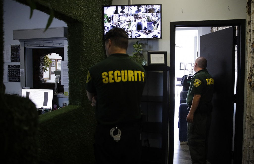 FILE - In this June 27, 2017 photo, two security guards stand watch at a medical marijuana dispensary in Los Angeles, a business conducted mostly in c