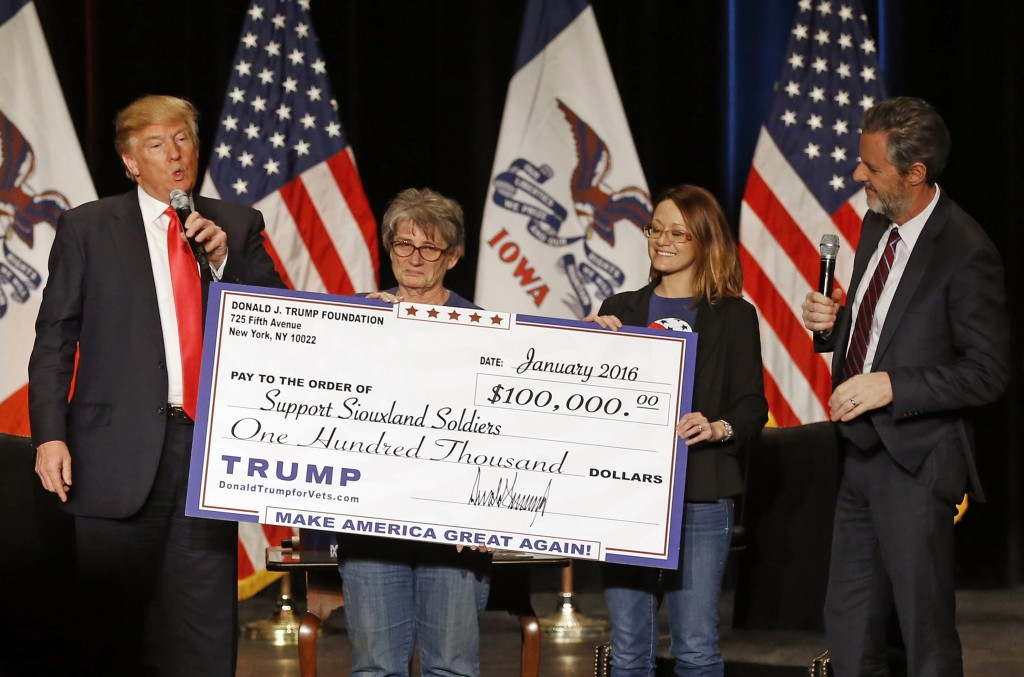 FILE - In this Jan. 31, 2016 file photo, Donald Trump, left, stages a check presentation with an enlarged copy of a $100,000 contribution from the Don