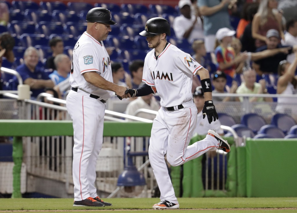 Miami Marlins third base coach Fredi Gonzalez, left, shakes hands with JT Riddle as he rounds the bases on a solo home run during the fifth inning of