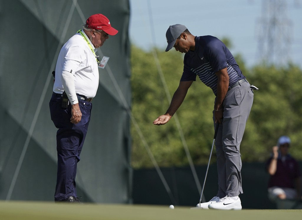 Tiger Woods, right, talks with an official on the tenth green after the wind moved his ball after he addressed it during the first round of the U.S. O