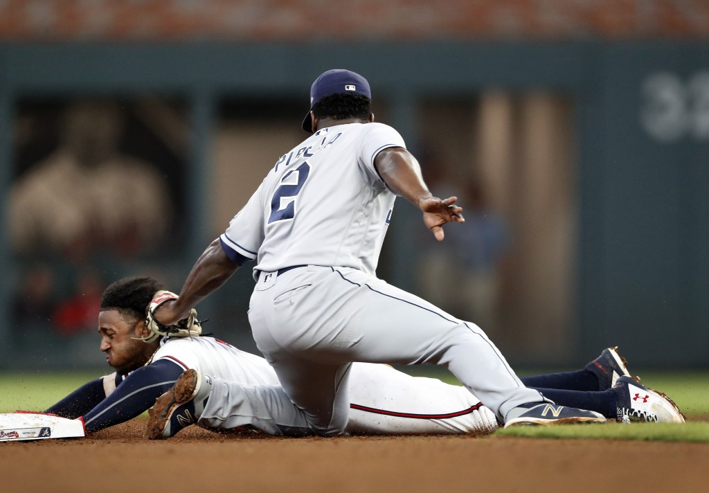 Atlanta Braves' Ozzie Albies is tagged out by San Diego Padres second baseman Jose Pirela (2) as he tries to steal second base during the fifth inning