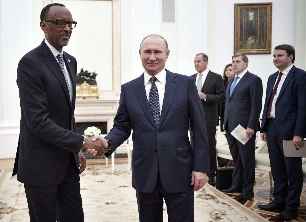 Russian President Vladimir Putin, center, and Rwanda's President Paul Kagame, left, shake hands while posing for a photo prior to their talks in Mosco
