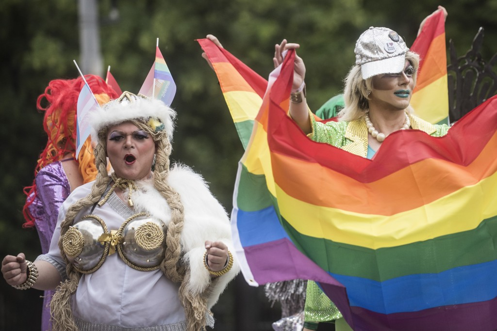 Gay and lesbian rights activists, one of them holding a rainbow flag, march during the annual Gay Pride parade, protected by riot police in Kiev, Ukra...