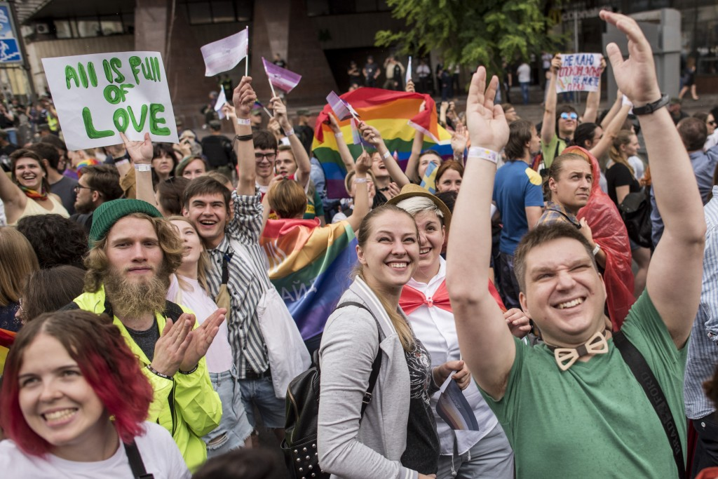 Gay and lesbian rights activists march during the annual Gay Pride parade, protected by riot police in Kiev, Ukraine, Sunday, June 17, 2018. Several t...