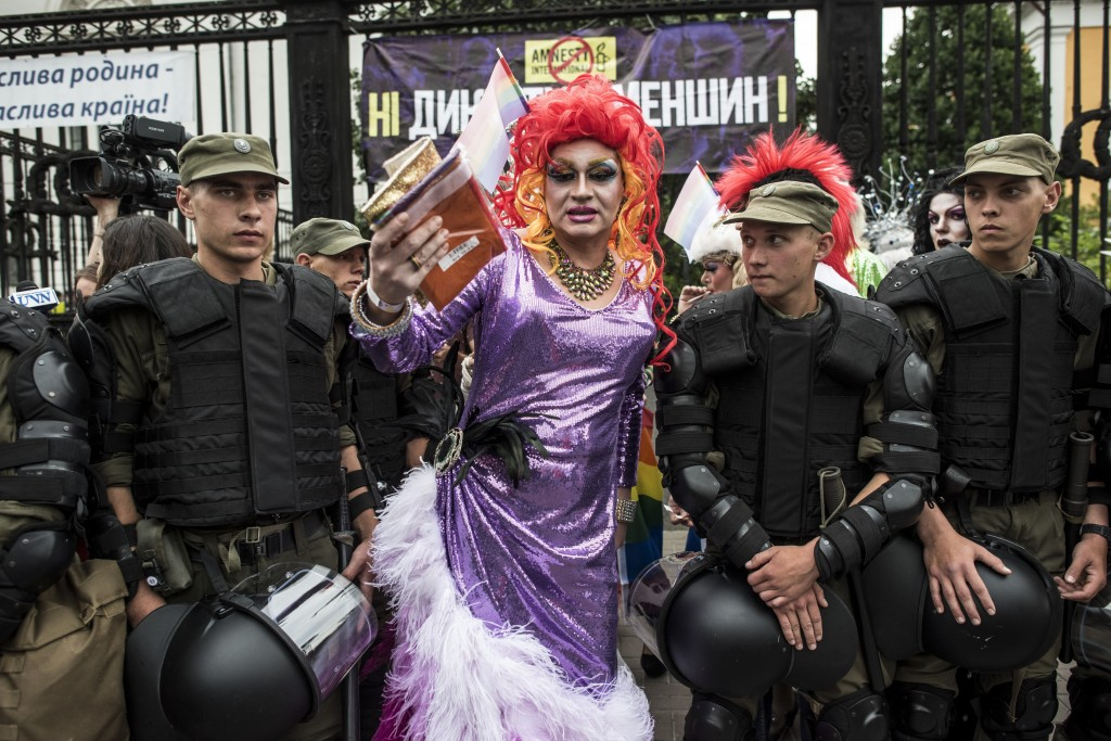 A gay and lesbian rights activist stands between Ukrainian police guards during the annual Gay Pride parade, protected by riot police in Kiev, Ukraine