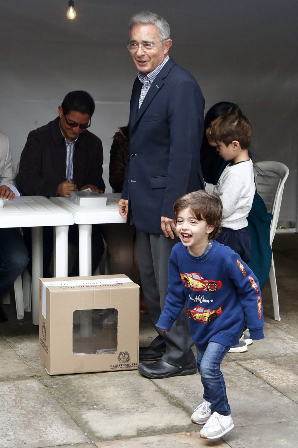 Former President Alvaro Uribe looks at a grand child after voting during the presidential runoff election in Bogota, Colombia, Sunday, June 17, 2018. ...