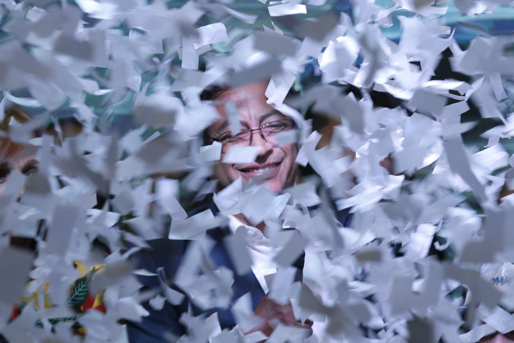 Gustavo Petro, presidential candidate for Colombia Humana, smiles surrounded in ticker tape while he speaks to his supporters, after his rival Ivan Du...