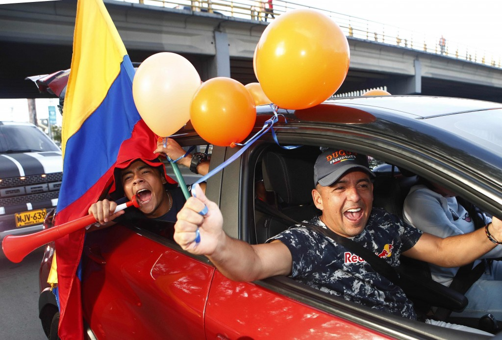 Supporters of Ivan Duque, candidate of the Democratic Centre party, celebrate the incoming results of the presidential runoff election in Bogota, Colo...
