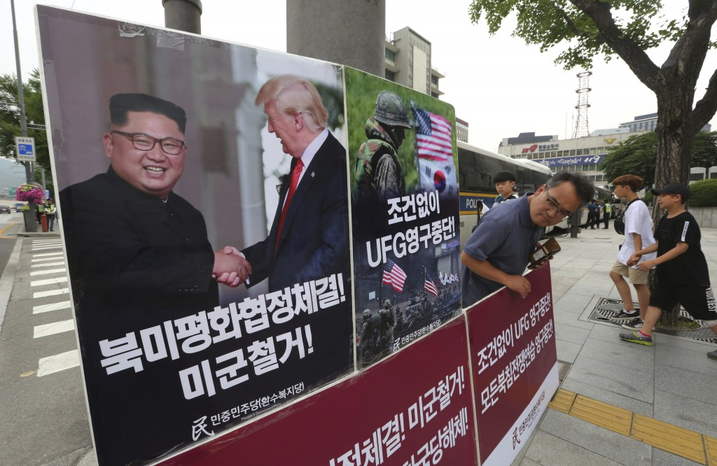 A photo showing U.S. President Donald Trump and North Korean leader Kim Jong Un is displayed as a member of People's Democratic Party stands to oppose