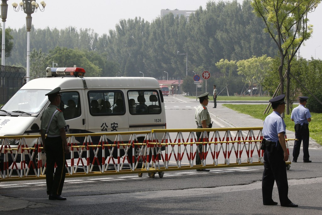 Paramilitary policemen and policemen seal off a road near the main entrance gate of the VIP gate of Beijing Capital International Airport as they prep...