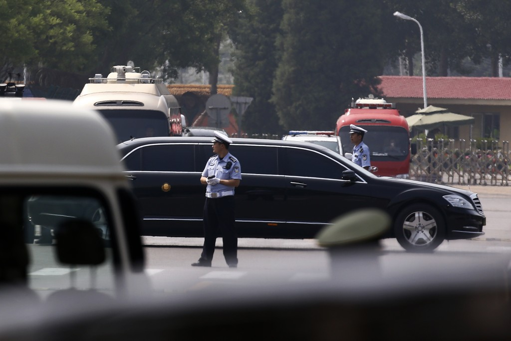 The motorcade which is believed to be carrying North Korea leader Kim Jong Un passes by policemen as it leaves the Beijing Capital International Airpo...