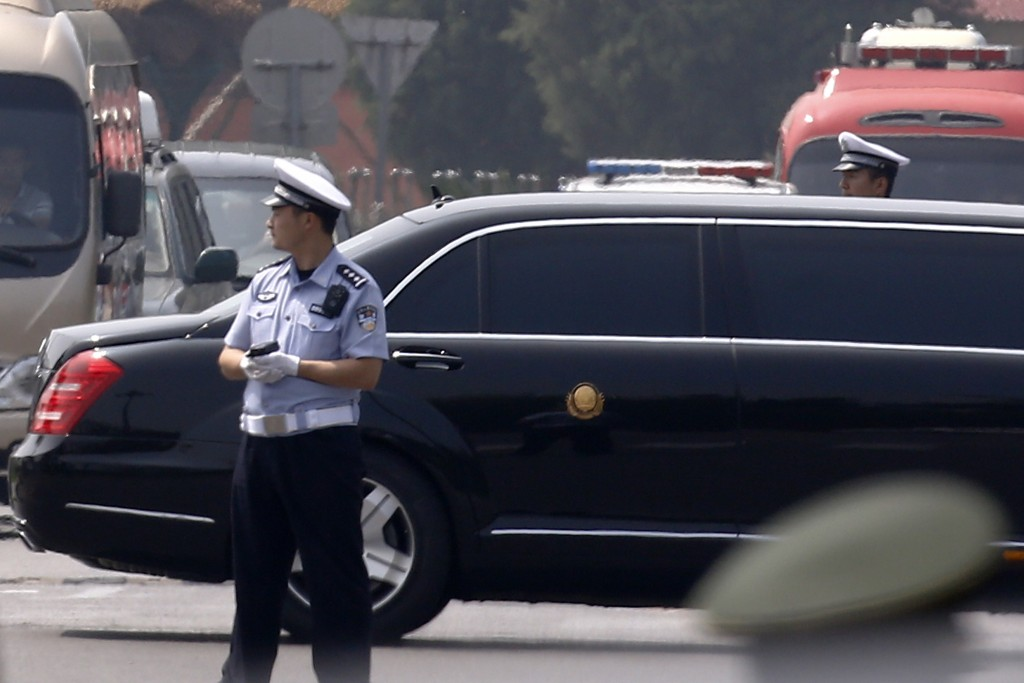 The motorcade that is believed be carrying North Korea leader Kim Jong Un,  passes by policemen as it leaves the Beijing Capital International Airport...