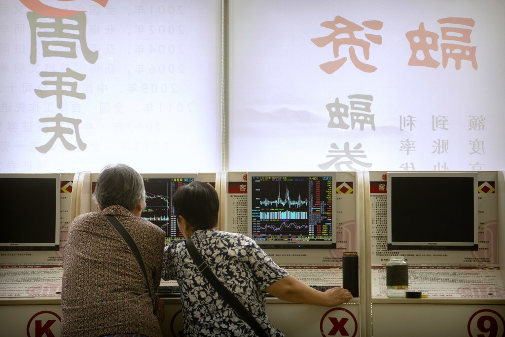 Chinese investors use computer terminals as they monitor stock prices at a brokerage house in Beijing, Friday, June 22, 2018. Asian stocks fell Friday...