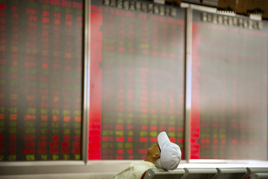 A Chinese investor sits at a brokerage house in Beijing, Friday, June 22, 2018. Asian stocks fell Friday following Wall Street losses overnight as inv...