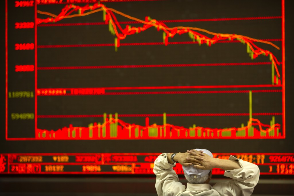 A Chinese investor monitors stock prices at a brokerage house in Beijing, Friday, June 22, 2018. Asian stocks fell Friday following Wall Street losses...