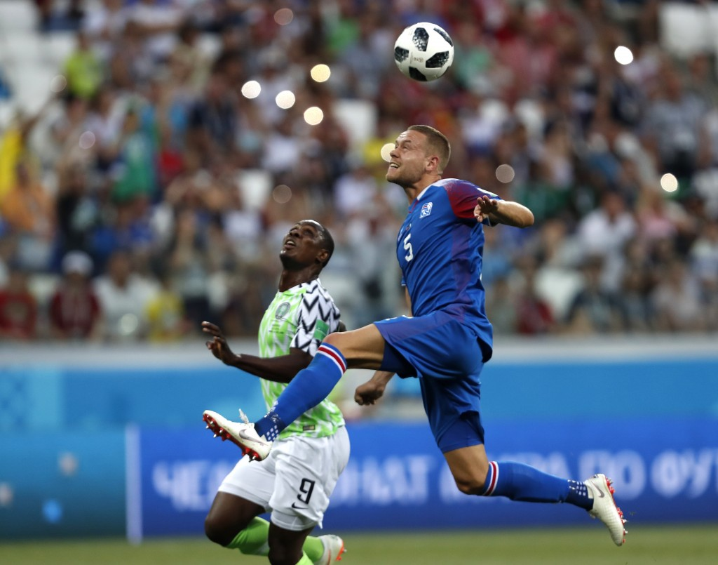 Iceland's Sverrir Ingason, right, leaps as he heads the ball clear of Nigeria's Odion Ighalo the group D match between Nigeria and Iceland at the 2018...