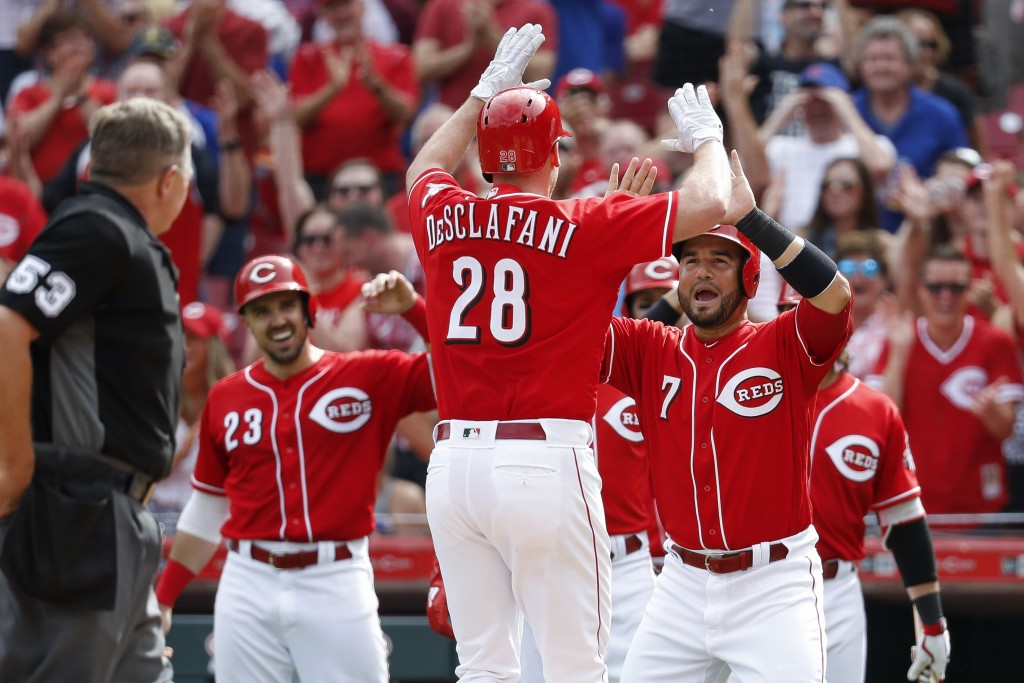 Cincinnati Reds' Anthony DeSclafani (28) celebrates with Eugenio Suarez (7) after hitting a grand slam off Chicago Cubs relief pitcher Brian Duensing ...