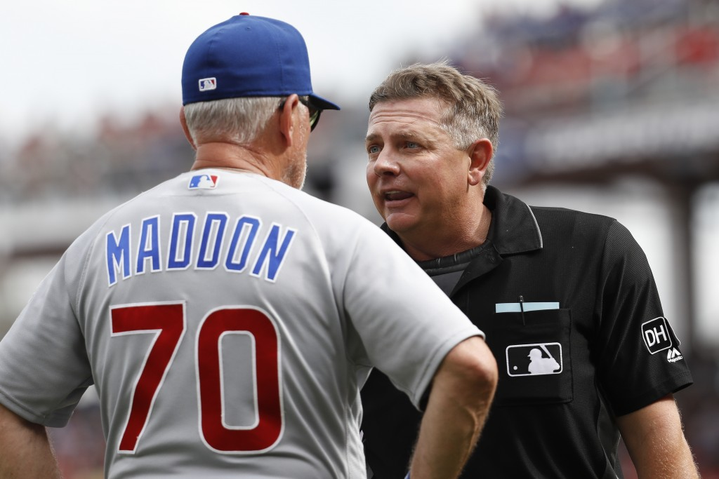 Umpire Greg Gibson, right, argues with Chicago Cubs manager Joe Maddon (70) after throwing out Chicago's bench coach Brandon Hyde for arguing with him...