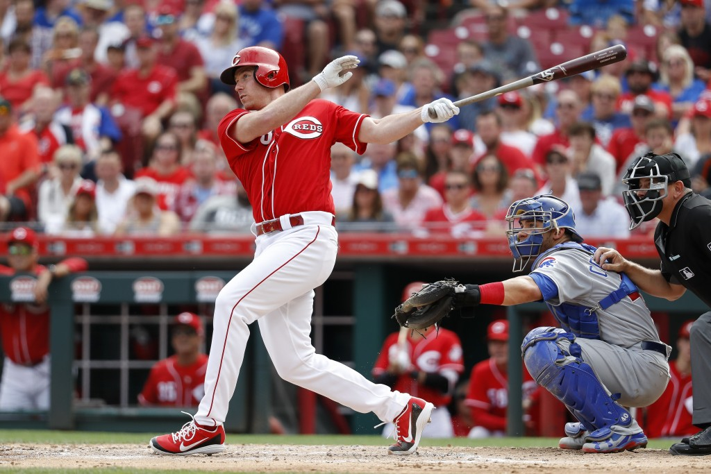 Cincinnati Reds' Anthony DeSclafani, left, hits a grand slam off Chicago Cubs relief pitcher Brian Duensing in the third inning of a baseball game, Sa...