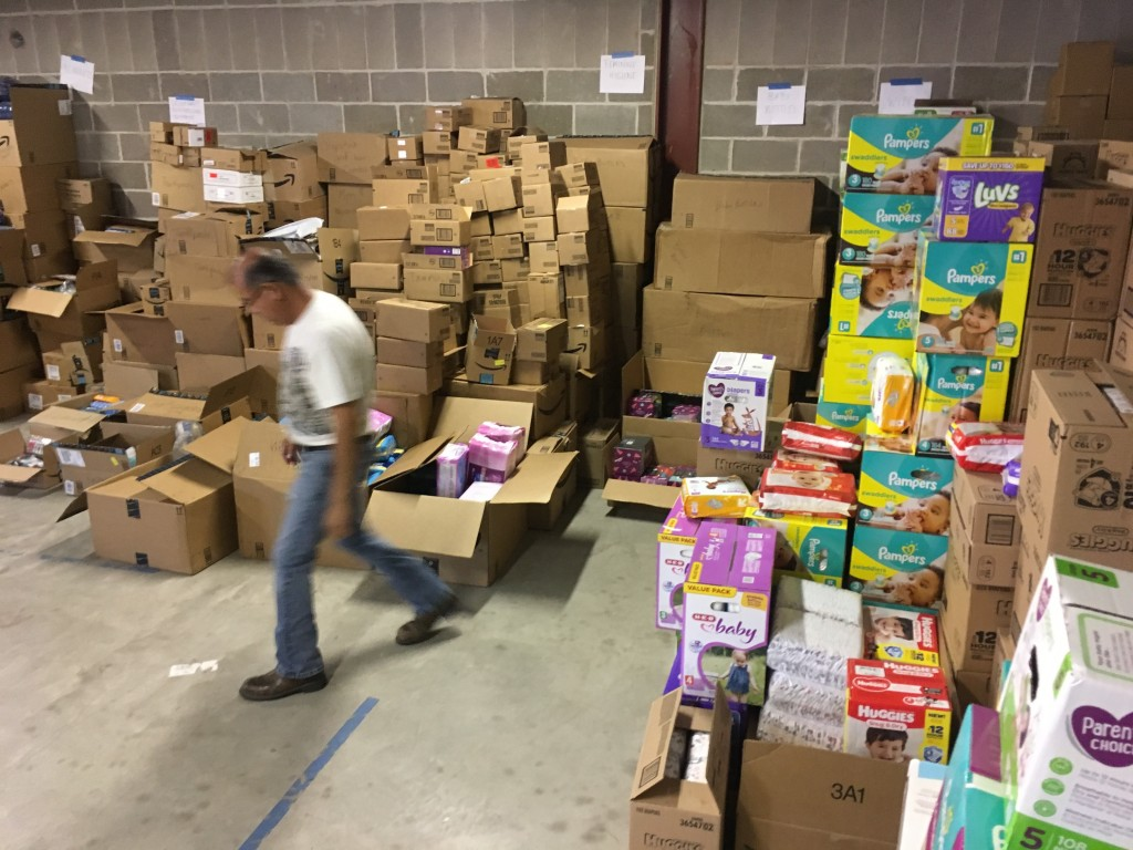 In this photograph taken June 24, 2018, Catholic Charities of the Rio Grande Valley staffer Eli Fernandez walks by boxes of donations at a storage fac...
