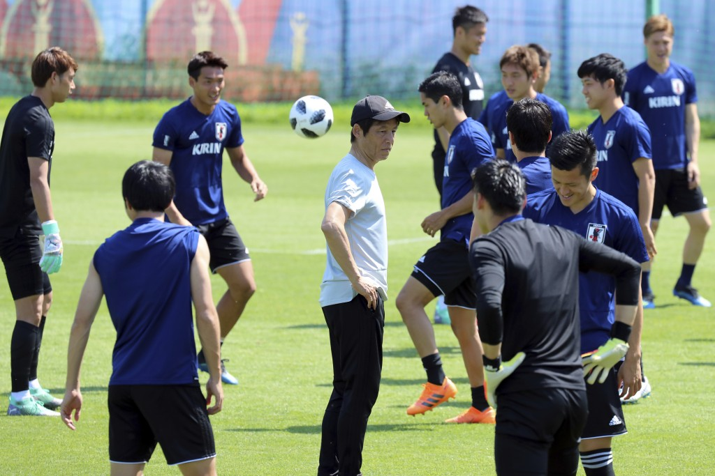 Players warm up as Japan's head coach Akira Nishino, center, watches during a training session of Japan national team at the 2018 soccer World Cup in