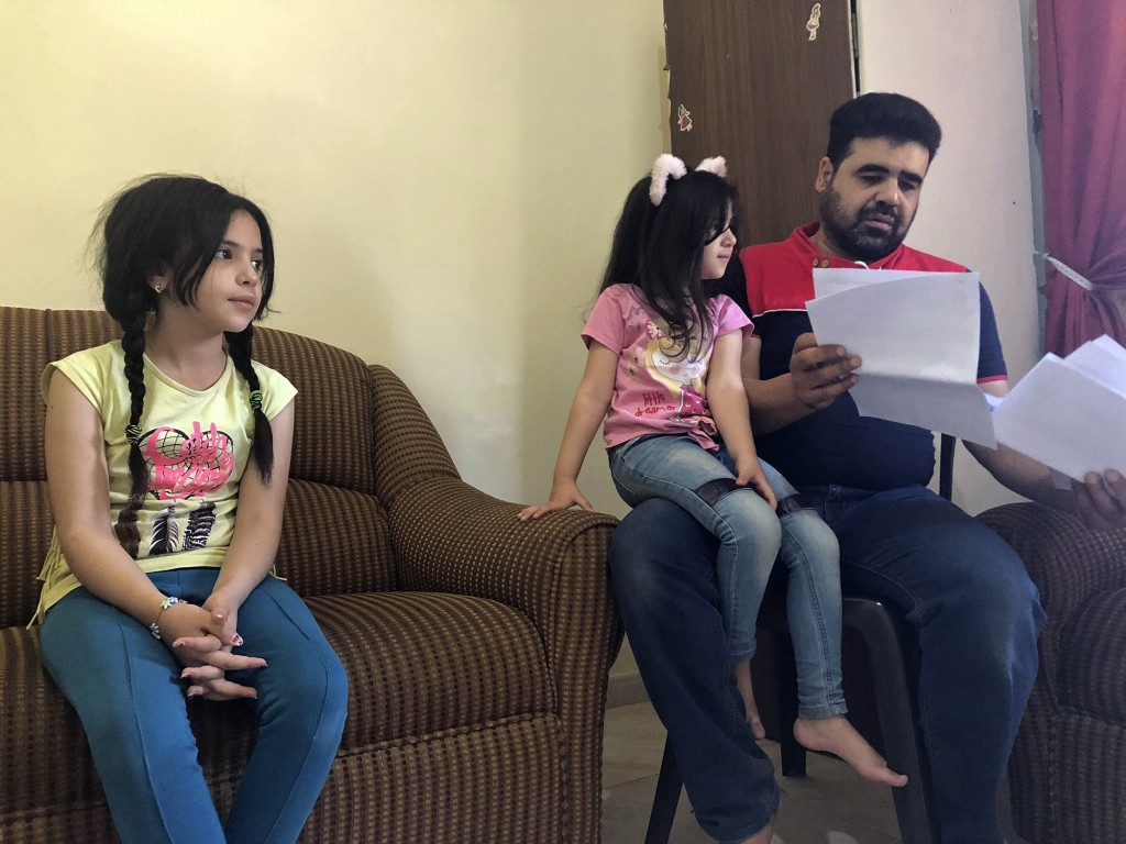 Syrian refugee Mahmoud Mansour, sitting with his daughters Sahar, 5, and Ruba, 11, holds documents for his U.S. resettlement application at his rented...