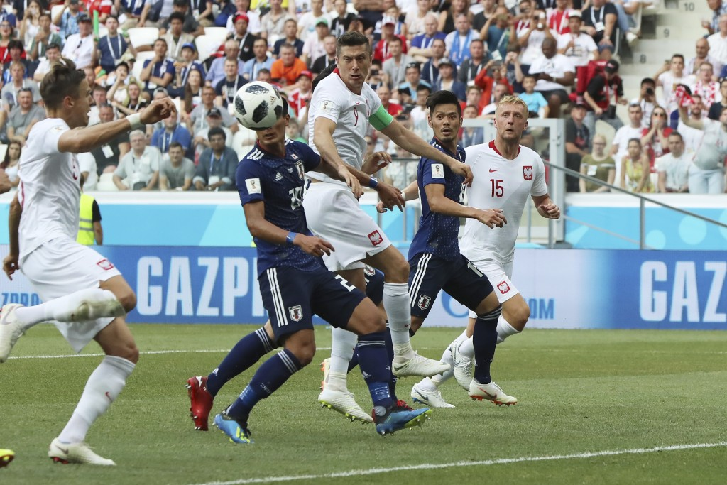 Poland's Jan Bednarek, left, scores his side's first goal during the group H match between Japan and Poland at the 2018 soccer World Cup at the Volgog