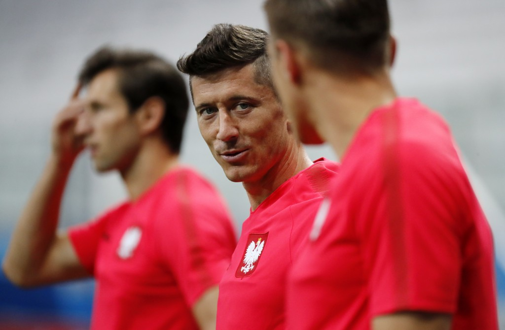 Poland's Robert Lewandowski, center, and other players warm up during Poland's official training on the eve of the group H match between Poland and Ja...