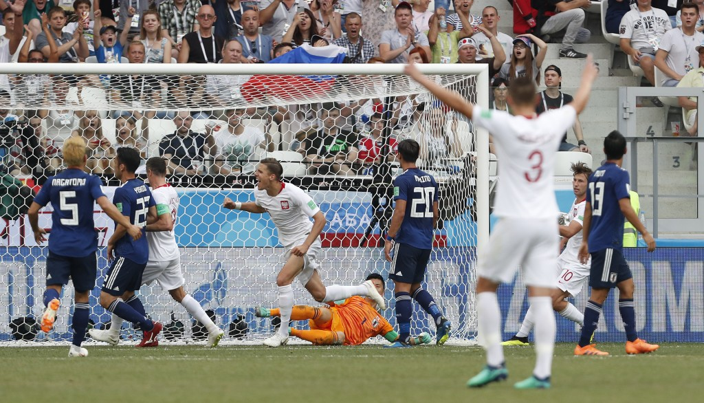 Poland's Jan Bednarek, centre, scores the opening goal during the group H match between Japan and Poland at the 2018 soccer World Cup at the Volgograd