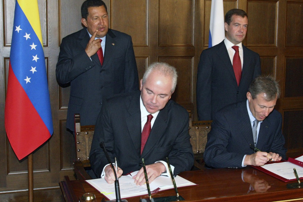 FILE - In this July 22, 2008 file photo, TNK-BP executive director German Khan, foreground left, signs papers, accompanied by Russian President Dmitry...