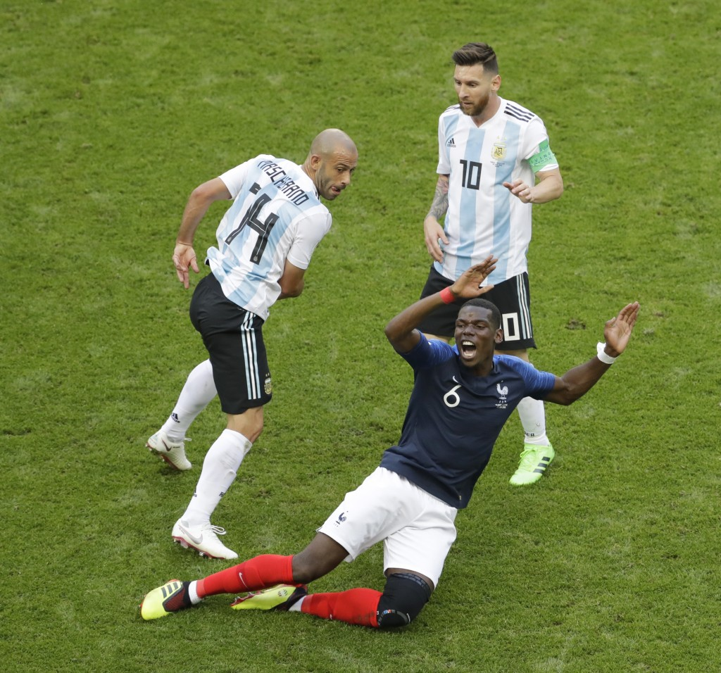 France's Paul Pogba, front, falls beside Argentina's Javier Mascherano, left, and Lionel Messi during the round of 16 match between France and Argenti...